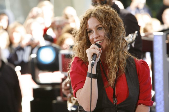 Alanis Morissette, red short-sleeved blouse, black vest, necklace, microphone