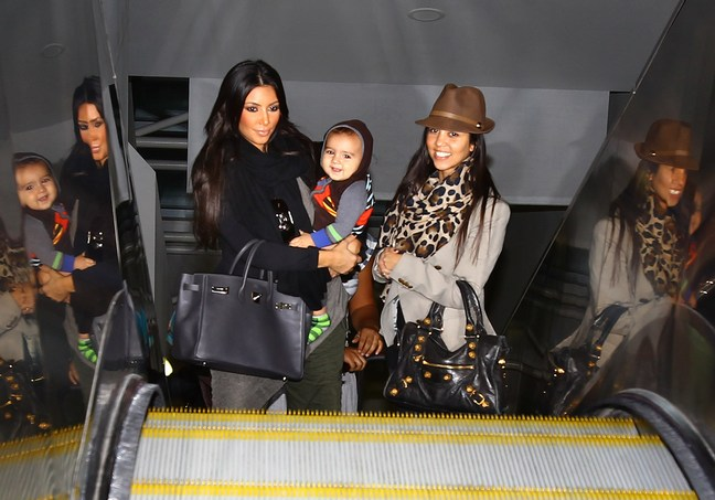 Kourtney Kardashian, Kim Kardashian, animal print scarf, brown hat, black tote bags, black sweater, airport