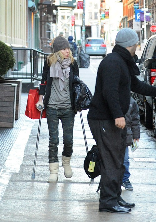 kelly ripa knit hat, crutches, boots, jeans, black jacket, scarf