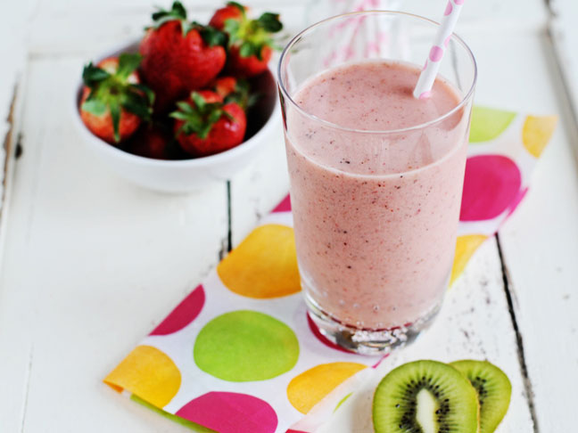 Fresh Strawberry Kiwi Smoothie in a clear tall glass with a bowl of strawberries in the background