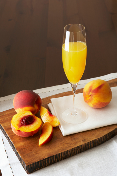 A peach bellini in a champagne glass
