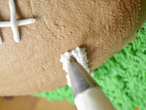Piping the stripes on the football cake