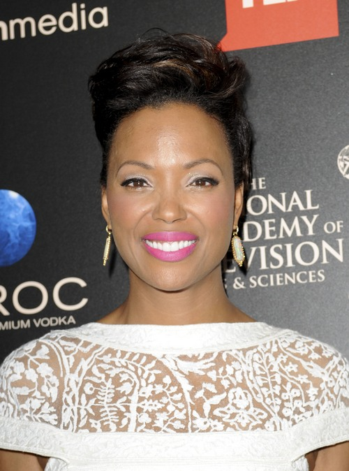 Aisha Tyler pictured smiling in a lace white dress