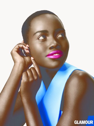Lupita Nyongo in a blue sleveless blouse and bright fuschia lips