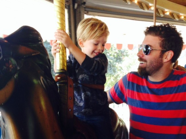 A little boy with his father rides the merry go round