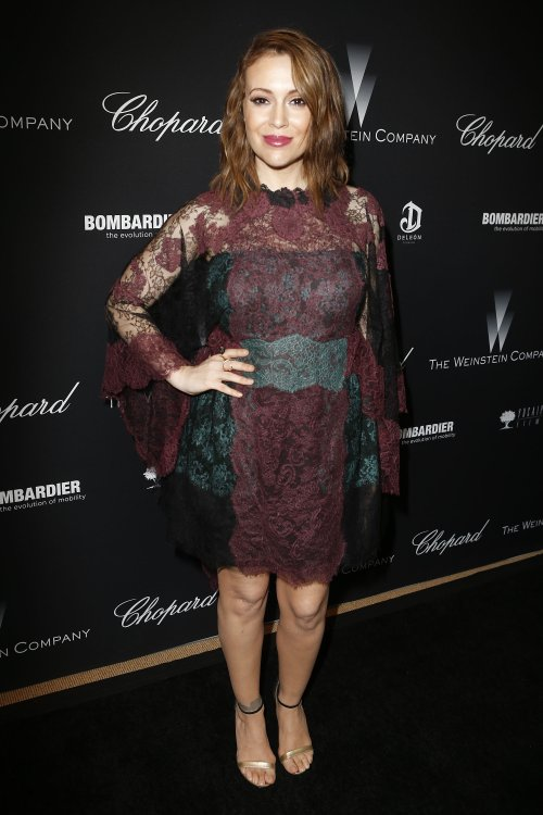 alyssa milano on the red carpet in a burgundy and black lace dress