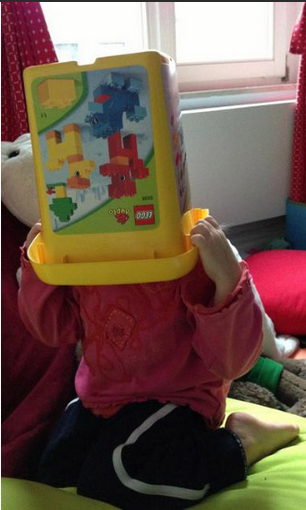 Child pulling lego box over head