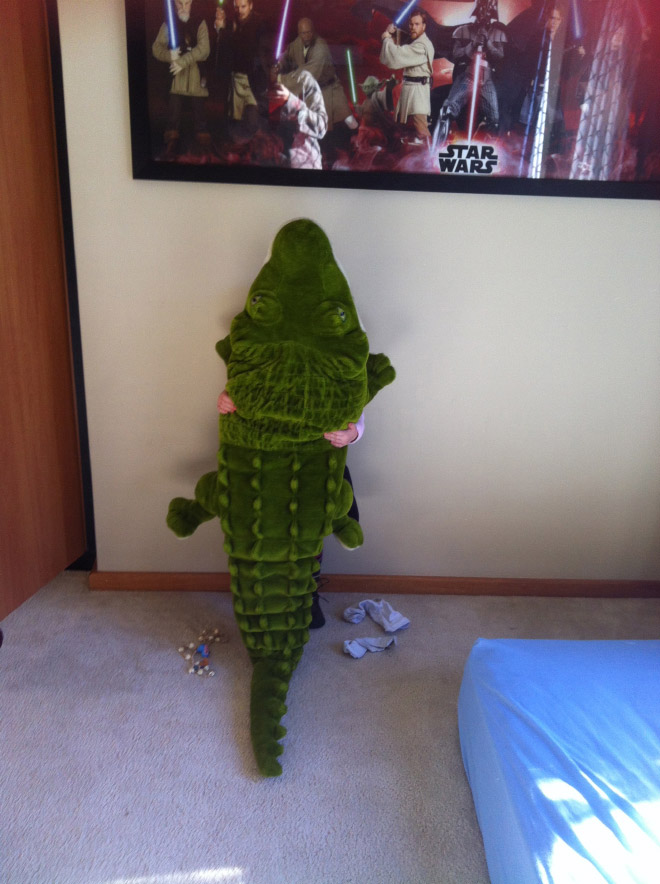 Little boy hiding behind alligator stuffed animal