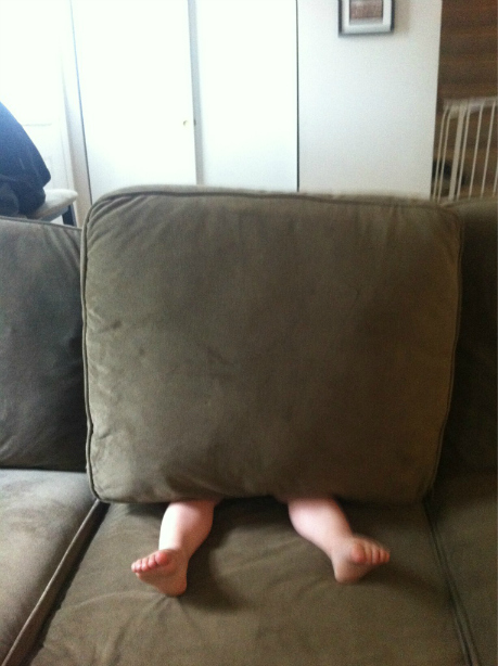 child hiding behind a pillow