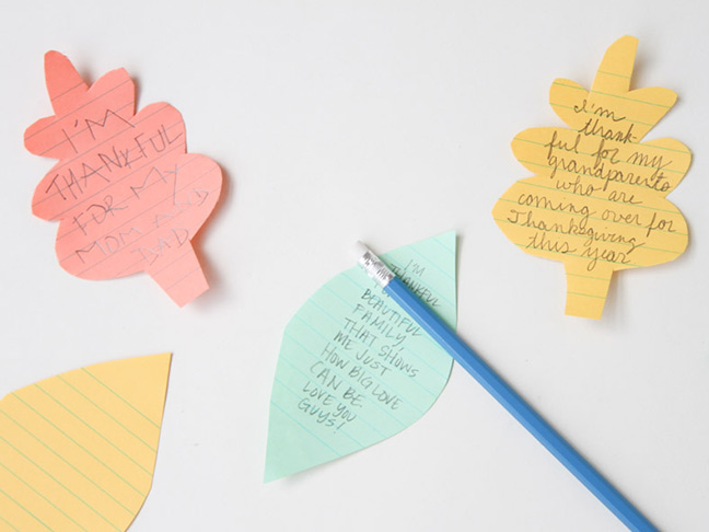Write messages on paper leaves for Thanksgiving