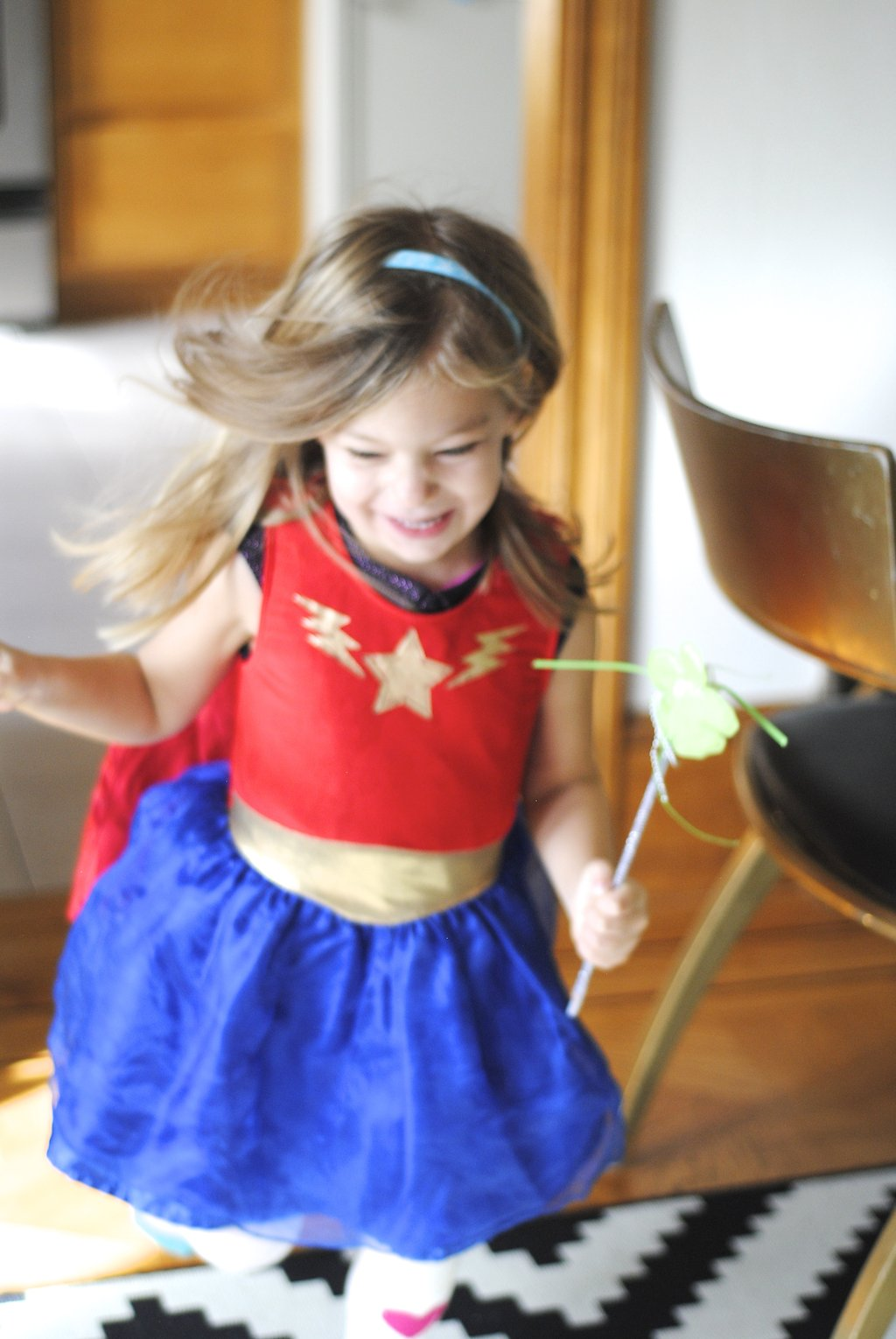 little girl running in superhero outfit