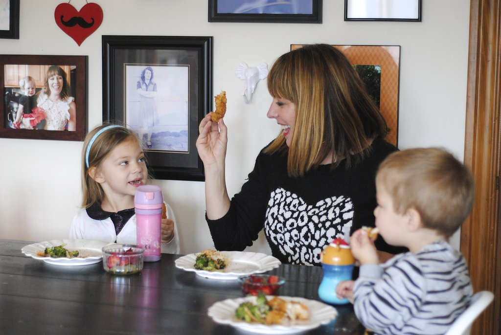 mom with kids laughing while eating dinner