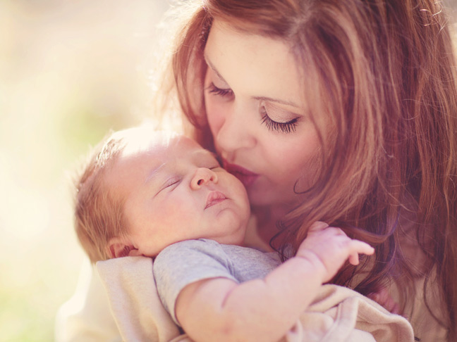mom-kissing-baby-outdoors