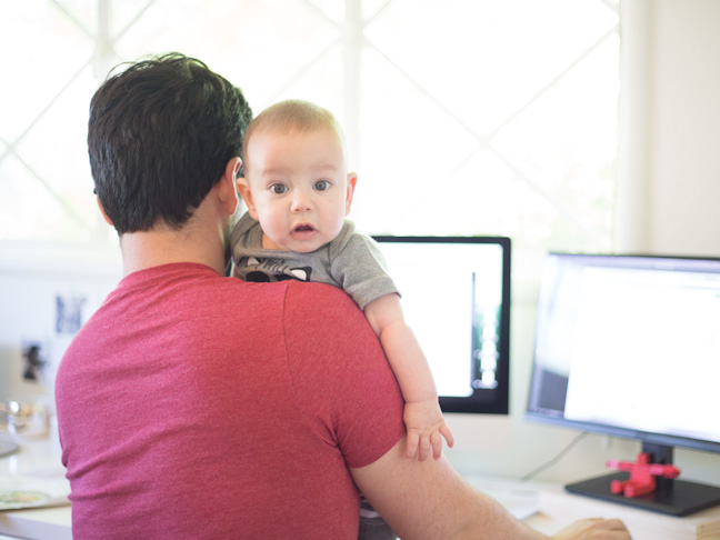 man working on computer holding baby