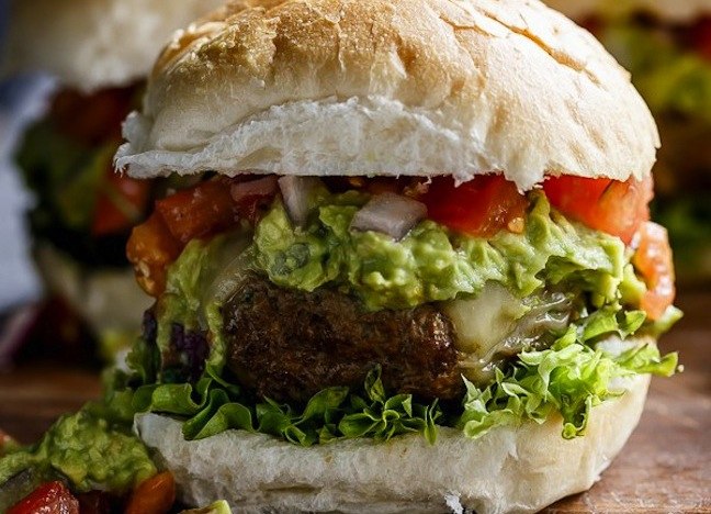 burger with guacamole and tomatoes