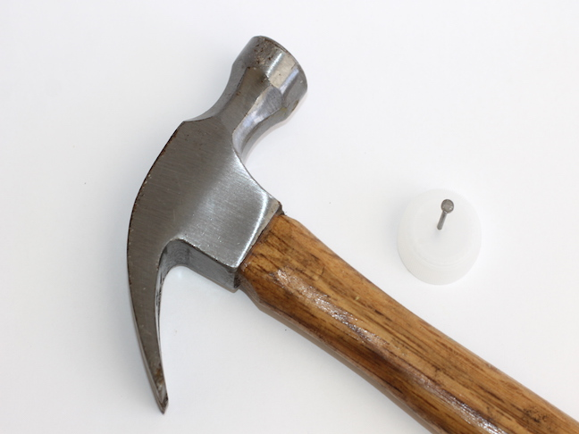 hammer with nail in bottle cap