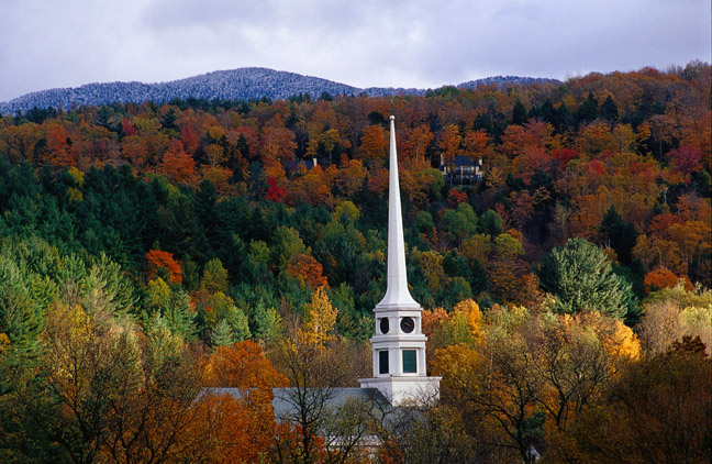 A church spire pierces the autumnal foliage around Stowe - Vermont