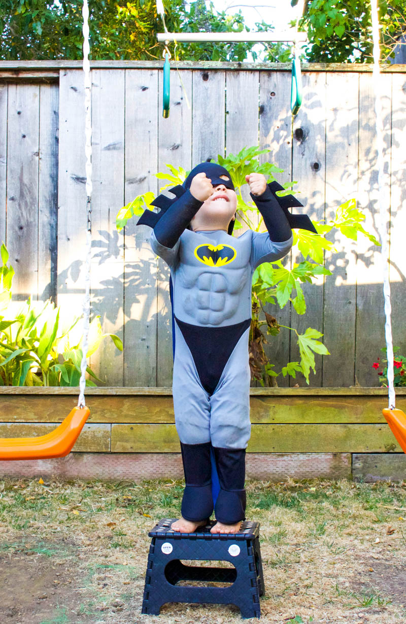 little boy as batman at swing set