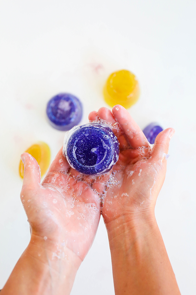 hands holding a purple disc of soap