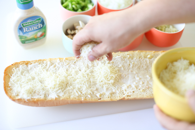 sprinkling cheese on garlic bread