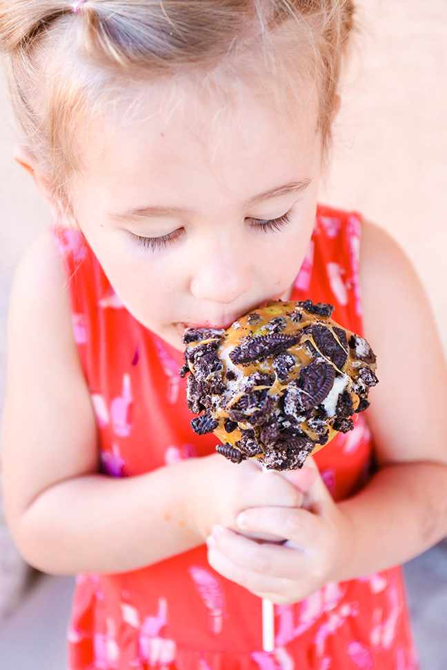 closeup of girl eating caramel apple with oreos