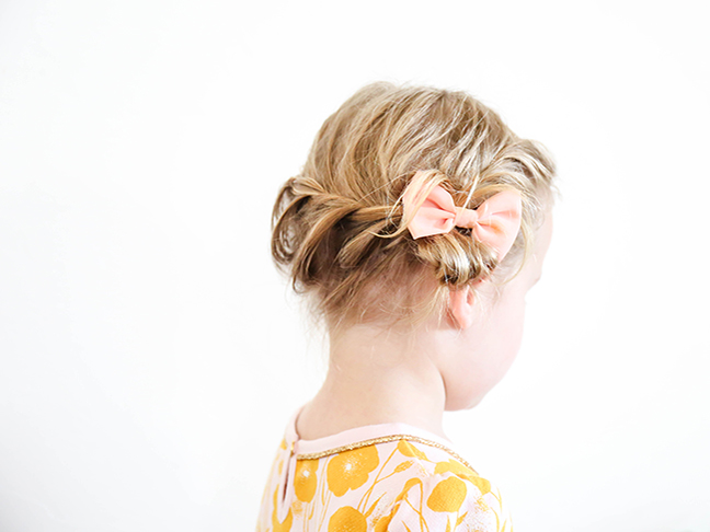braided toddler hair with peach bow