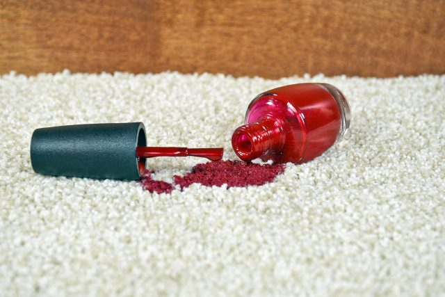 Close up of bright red nail polish on light colored carpet