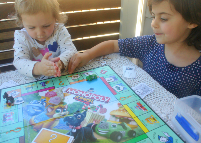 Siblings playing together on Monopoly Junior.