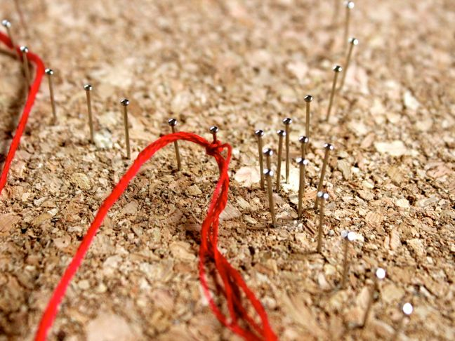 red-string-tied-around-a-pin-pushed-into-a-cork