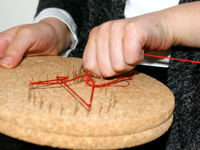 hands-crafting-a-diy-string-art-with-red-string-and-pins-on-a-cork